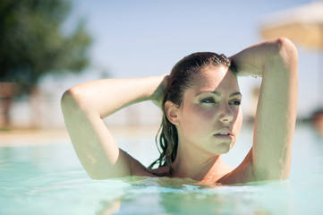 Sensual woman close up portrait in swimming pool.