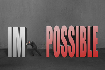 "Businessman push ""IM"" of ""IMPOSSIBLE"" away to make it possible"