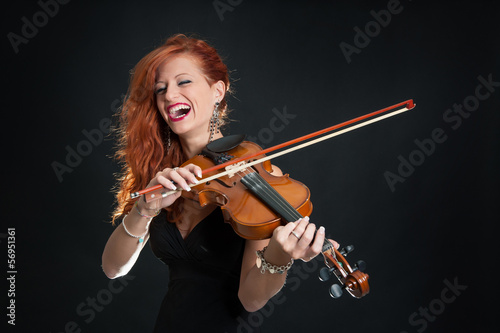 Young woman playing violin against black background.