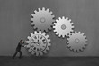 Businessman rolling a large concrete gear with clock drawing and
