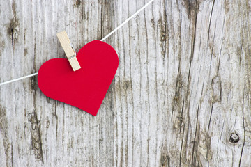 red heart hanging on line against old wood-grain wall