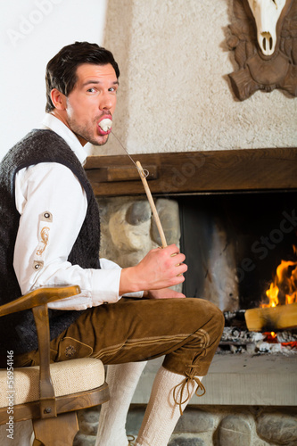 Young man in hunter's cabin eating marshmallow