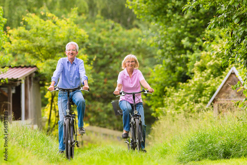 Leinwanddruck Bild Seniors exercising with bicycle
