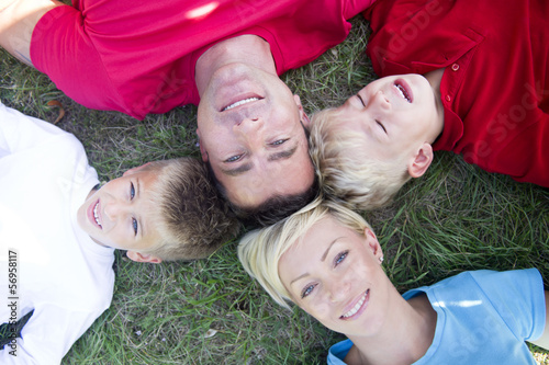 Family laying on ground with heads touching