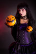 Beautiful witch holding Jack lantern oranges