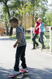 Young boy skateboarding as parents watch