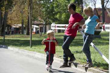 Young boy on unicycle with parents watching