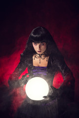Beautiful gothic style fortune teller with a crystal ball