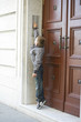 Young boy on tiptoes ringing doorbell