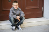 Young boy sitting on doorstep