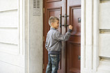 Young boy knocking on big wooden door