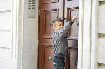 Young boy ringing doorbell