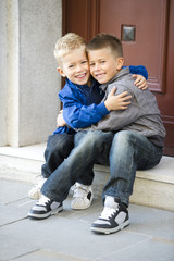 Two young boys hugging each other