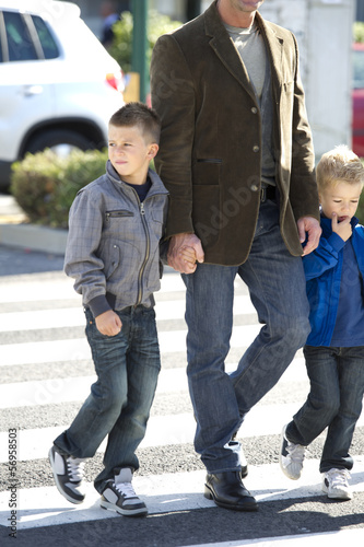 Father and sons walking across street