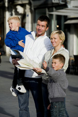 Young family looking at map in the city