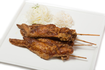 Fried chicken wings with sauce on skewers with rice