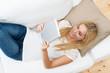 schöne blonde frau liest ein ebook auf dem sofa