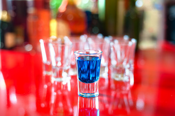 Blue hot alcoholic drink in shot glass on bar