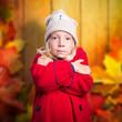 kleines frierendes Mädchen vor Herbsthintergrund