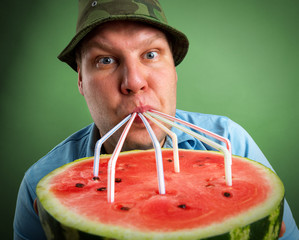 Bizarre farmer drinking watermelon juice through a tubules