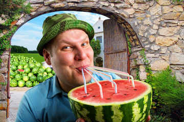 Cheerful farmer drinking watermelon