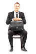 Young businessman in black suit holding a briefcase and waiting