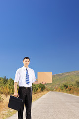 Young businessman with suitcase and cardboard hitchhiking