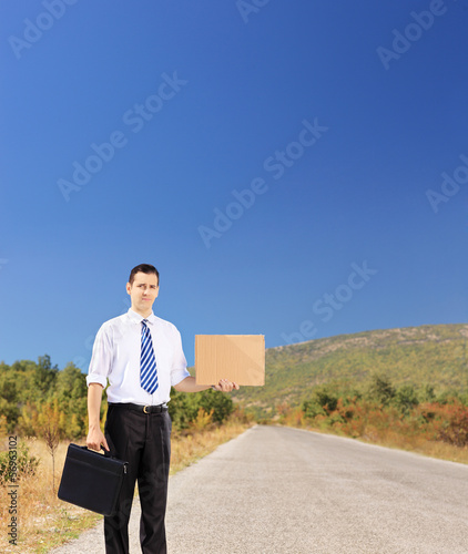 Young businessperson holding suitcase and hitchhiking on a road