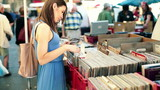 Young woman looking at old vinyl records on flea market
