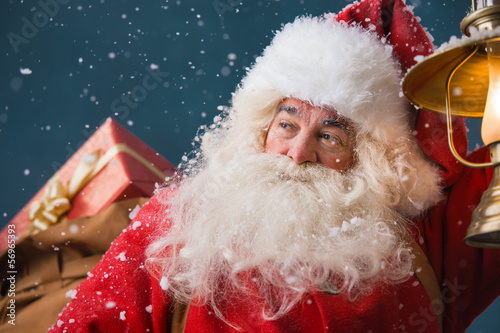 Santa Claus walking on the snow with his sack of gifts