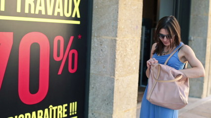 Disappointed woman with empty wallet looking at sale sign