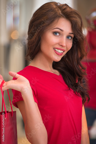 Smiling girl with shopping bags at store