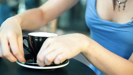Woman hands sweetening and mix coffee in cafe