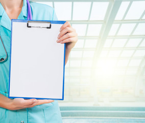 hands of female doctor holding clipboard