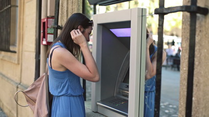 Young woman taking cash from ATM machine in the city