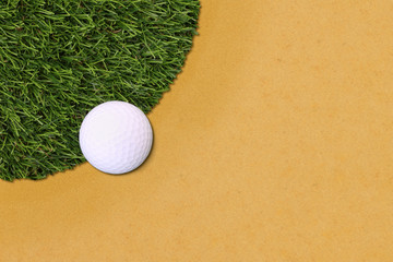 Golf ball edge of grass field and sand.