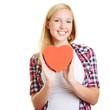 Junge Frau hält rotes Herz