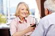 Seniorin trinkt Wein mit Mann im Restaurant