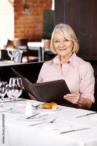 Seniorin im Restaurant mit der Speisekarte