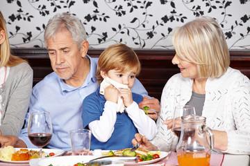 Kind wischt mit Serviette den Mund ab