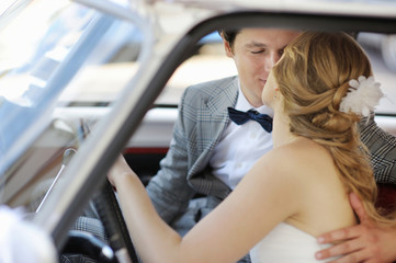 Bride and groom in a wedding car