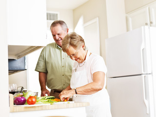 elderly married couple cooking dinner