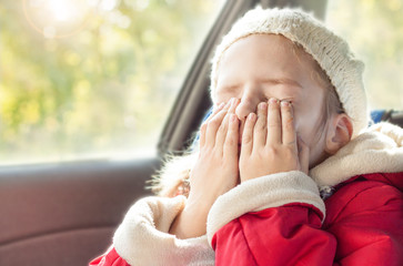 Small girl crying while traveling in a car seat during autumn