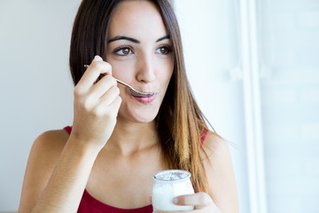 young woman at home eating yogurt