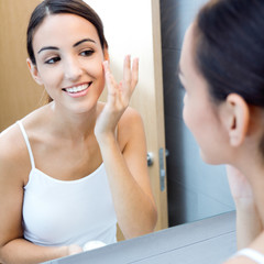 Portrait of young woman applying moisturizer cream on her pretty