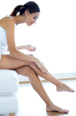 Body care. Woman applying cream on legs