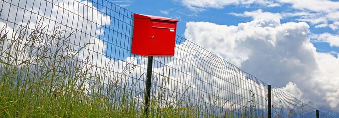 Roter Briefkasten am Zaun