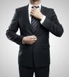 man adjusts his tie