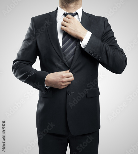 man adjusts his tie