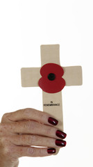 Woman's hand holding a Remembrance Day cross